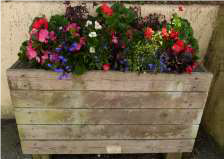 colourful flowers in a brown wooden tub